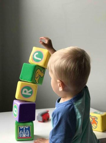 enfant jouant avec des cubes et faisant une construction