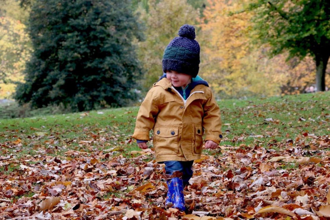 l'enfant marchant sur les feuilles d'automne